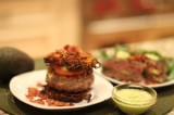 Avocado stuffed burger with pancetta and drizzled with green goddess dressing on a Sweet Potato Bun